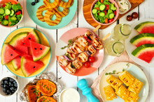 Summer BBQ Or Picnic Food Concept. Selection Of Grilled Meat, Fruits, Salad And Potatoes. Top View Table Scene Over A White Wood Background.