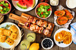 Summer picnic or BBQ food concept. Selection of fruits, salad, grilled meat and potatoes. Above view table scene over a wood background.