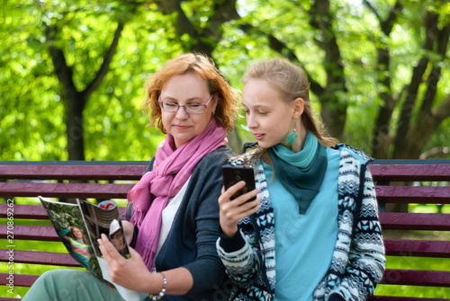 Vászonkép mom and daughter read a magazine in the park