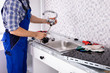 canvas print picture - Plumber Assembling The Kitchen Sink Faucet