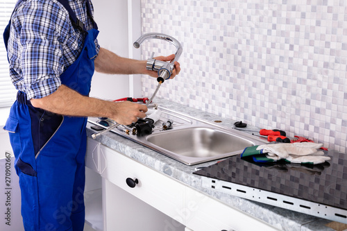 Photo sur Toile Kiev Plumber Assembling The Kitchen Sink Faucet