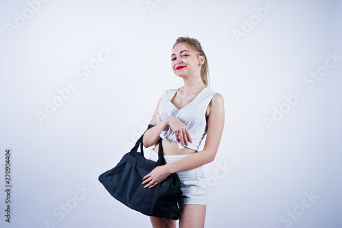 Amazing fit sexy body brunette caucasian girl posing at studio against white background on shorts and top with black sport bag Wallpaper Mural