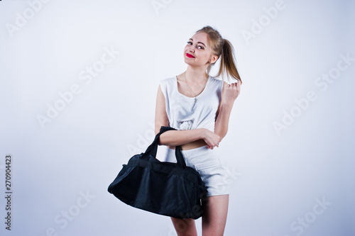 Amazing fit sexy body brunette caucasian girl posing at studio against white background on shorts and top with black sport bag Canvas Print