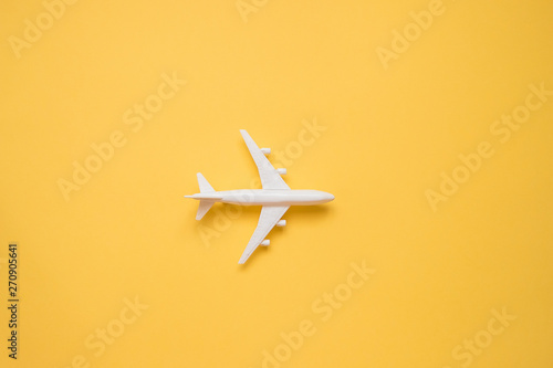 Obraz Flat lay design of travel concept with plane on yellow background with copy space. - fototapety do salonu