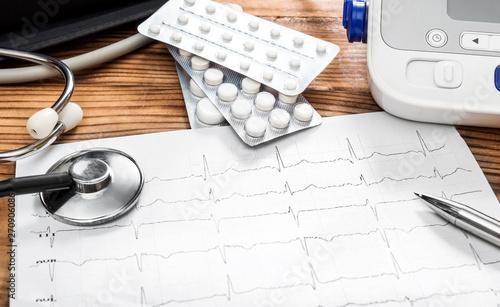Fotografia  Doctor's workplace with cardiogram, pills, stethoscope and tonometr