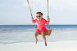 Happy Toddler Girl Swinging On Beach