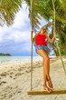 Happy tourist woman swinging on tropical beach under coconut palm trees of Anse Volbert Cote d'Or, Praslin, Seychelles, Indian Ocean. Lifestyle female enjoying in summer holidays. Vertical shot.