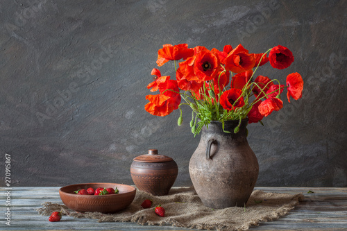 Photo  Still life in a rustic style: an old crock and a bouquet of red poppies and stra
