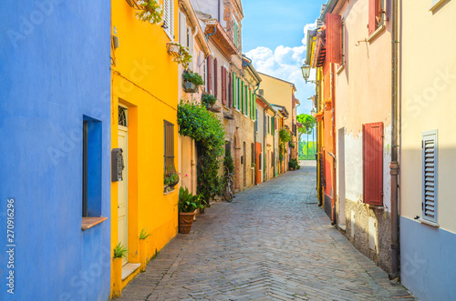 Typical italian cobblestone street with colorful multicolored buildings, traditional houses with green plants on walls and shutter windows in old historical city centre Rimini, Emilia-Romagna, Italy