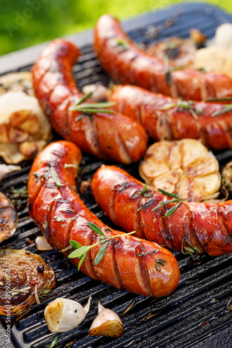 Fototapeta Grilled sausage with the addition of herbs and vegetables on the grill plate, close-up, outdoors. Grilling food, bbq, barbecue obraz