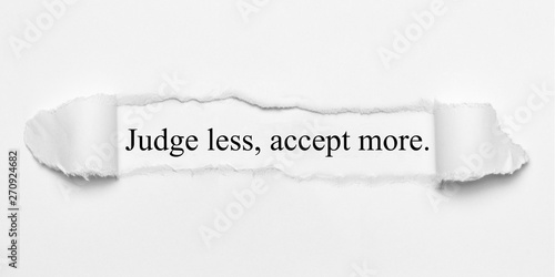 Photo Judge less, accept more. on white torn paper