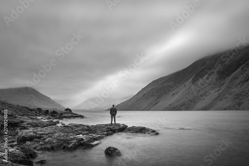Foto auf AluDibond Rosa dunkel Lone man in landscape image of Wast Water in UK Lake District during moody Spring evening in black and white