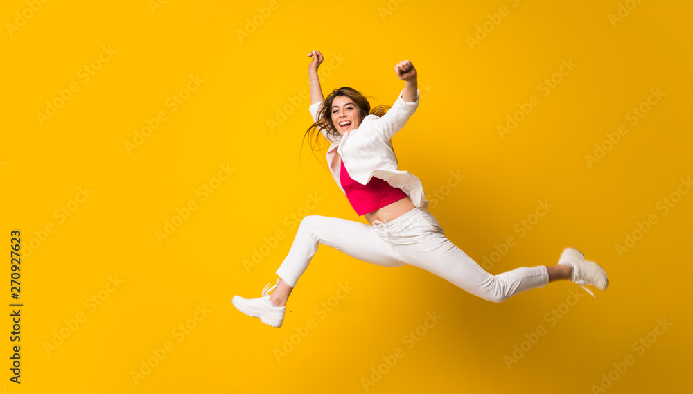 Fototapeta Young woman jumping over isolated yellow wall