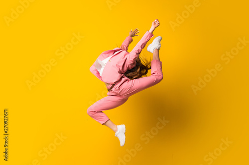 Young woman jumping over isolated yellow wall - 270927671