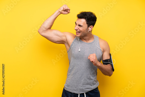 obraz lub plakat Handsome sport man over isolated background celebrating a victory