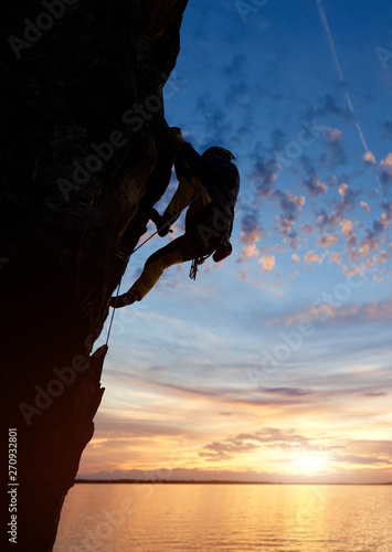 Silhouette of sport man climbing up to top of mountain summit Canvas Print