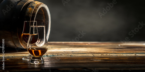Two glasses of whiskey standing against an oak barrel Fotobehang