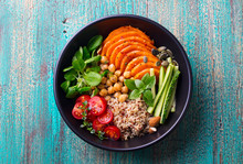 Healthy Vegetarian Salad. Roasted Pumpkin, Quinoa, Tomatoes, Green Salad. Buddha Bowl. Blue Wooden Background. Top View.