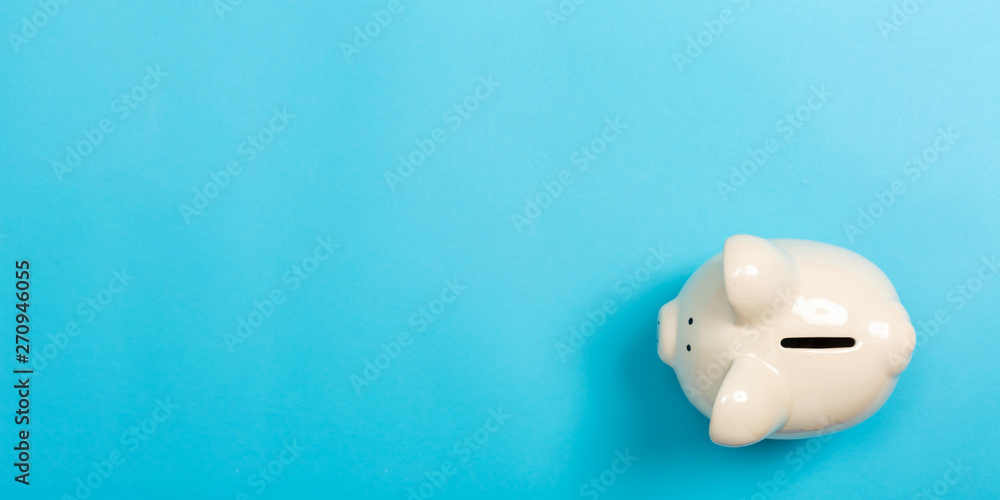 Fototapety, obrazy: A piggy bank saving and investment theme on a blue paper background