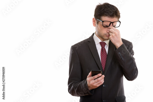 Foto auf Leinwand Texturen Studio shot of tired young businessman wearing eyeglasses while