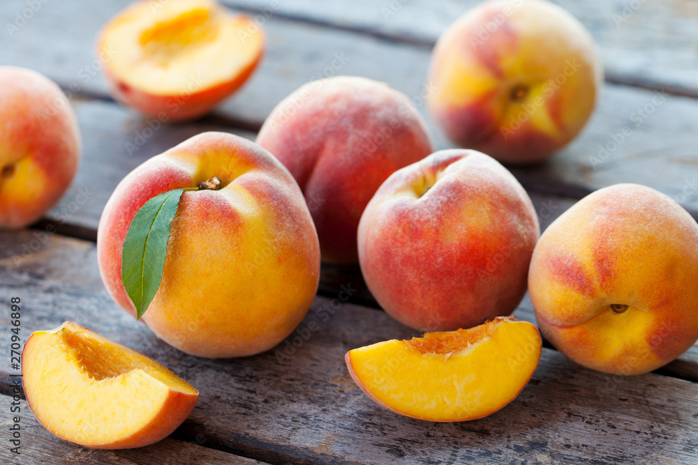 Fototapeta Fresh peaches, fruits on grey wooden background. Close up.