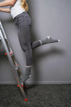 Unrecognizable Woman Climbing And Balancing On Ladder In Socks - Home Improvement Diy Or Household Accident Proneness Concept