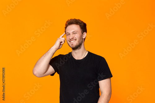 Obraz Studio shot of a bearded young man pointing a finger at the temple. Concept of a positive thinking. - fototapety do salonu