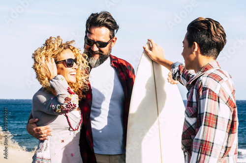 Fototapeta  beautiful family together forever at the beach with a sunny day and surfer teena