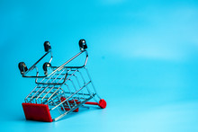 Shopaholic Phobia Concept By Collapsed Trolly Cart On Blue Background Space