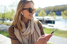 Pretty Young Woman Listening To Music With Wireless Earphones And The Smartphone In The Street.