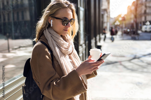 Fotografie, Obraz  Pretty young woman listening to music with wireless earphones and the smartphone in the street