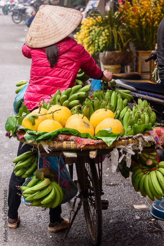 Fototapeta  A woman carries fruit in baskets strapped to her bicycle in Hanoi, Vietnam