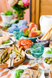 Dining table with different foods, snacks and flowers. Summer lunch in the open air. Seafood and vegetables.
