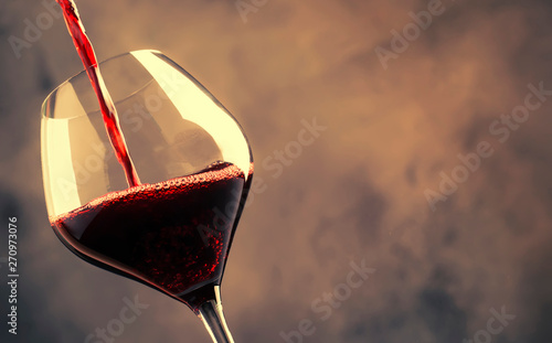 Stampa su Tela  French dry red wine, pours into glass, gray background, selective focus