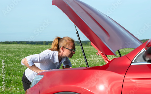 girl opens hood of car and looks puzzled inside. Wallpaper Mural