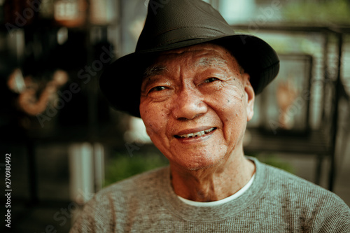 Foto  Asian senoir old man retirement drinking coffee in cafe smile and happy face
