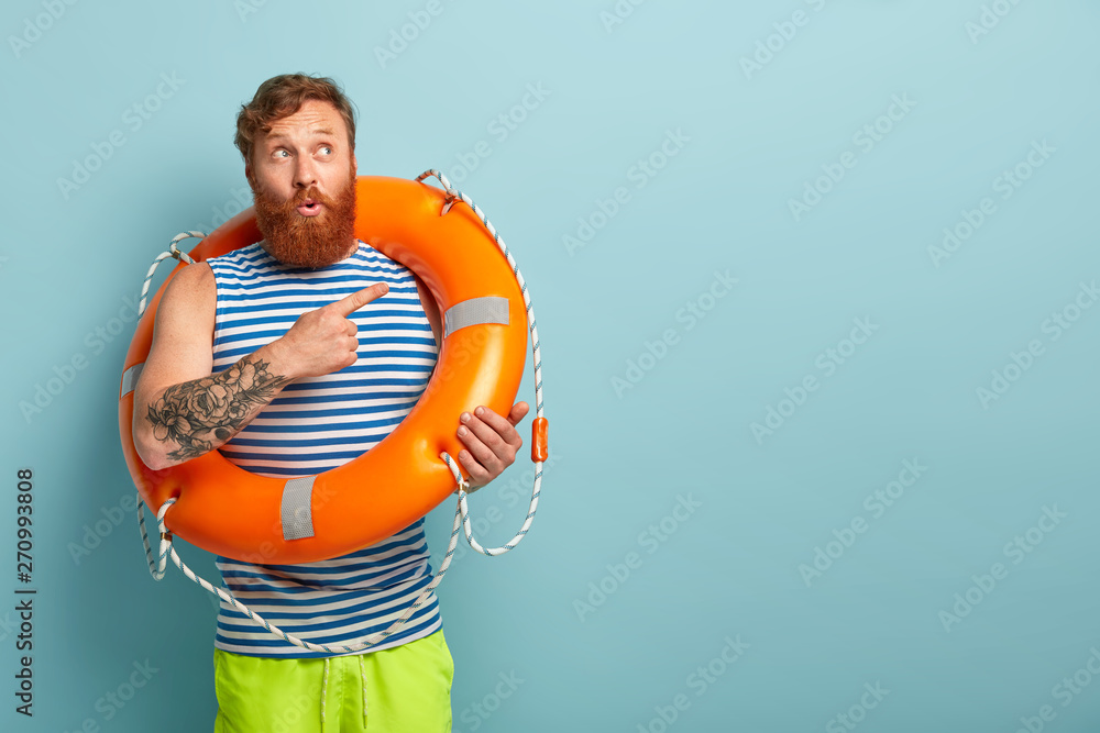 Fototapety, obrazy: Shot of puzzled surprised redhaired male rescuer with lifebuoy, shows direction, points at upper right corner, tells impressive story about saving sinking person. Man on awesome summer vacation