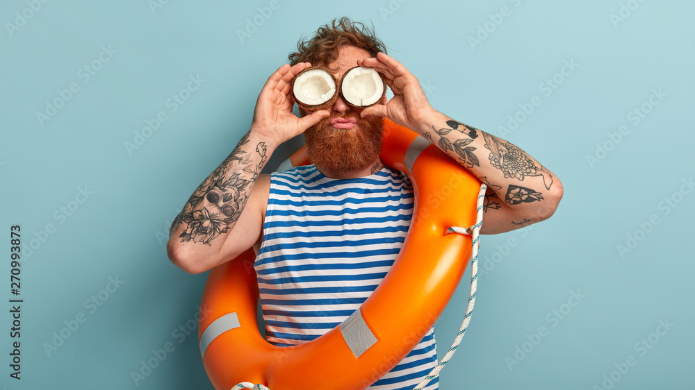 Fototapety, obrazy: Curly red haired man keeps cocnonut on eyes, has fun near water, feels bored working as liveguard, wears sailor vest, stands over blue background, carries orange lifebuoy for saving people at beach