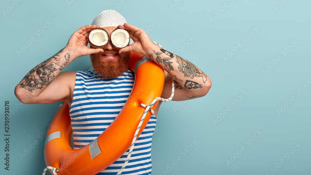 Fototapety, obrazy: Male safeguard supervises situation on sea, holds two coconuts on eyes instead of binoculars, wears white swimhat, sailor vest, uses safety equimpent like ring buoy, poses over blue wall, blank space