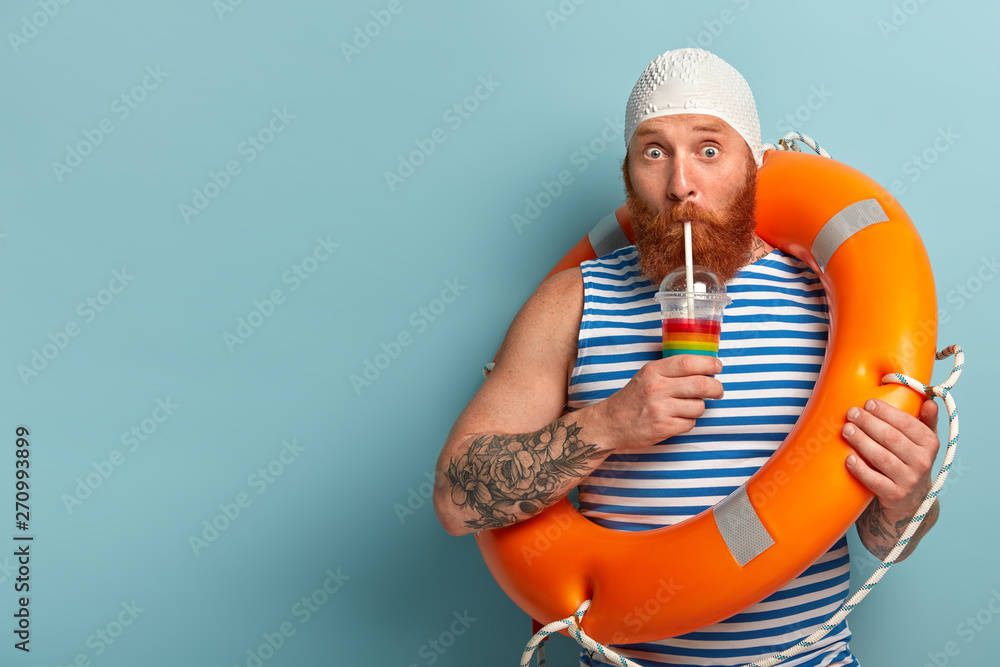 Fototapety, obrazy: Embarrassed holiday maker drinks cold summer cocktail, spends free time at beach, wears swimcap sailor t shirt, swims with lifebuoy, has surprised expression, models over blue wall with free space