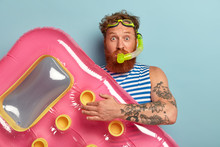 Studio Shot Of Surprised Bearded Red Man Wears Snorkel Mask, Holds Pink Inflated Mattress, Wears Sailor T Shirt, Ready For Snorkeling In Sea Or Ocean Enjoys Underwater Activities Isolated On Blue Wall