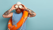 Male Safeguard Supervises Situation On Sea, Holds Two Coconuts On Eyes Instead Of Binoculars, Wears White Swimhat, Sailor Vest, Uses Safety Equimpent Like Ring Buoy, Poses Over Blue Wall, Blank Space