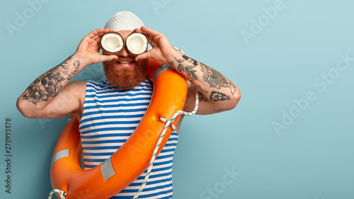 Fotomural  Male safeguard supervises situation on sea, holds two coconuts on eyes instead o
