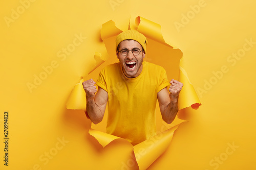 Fototapeta Yeah, we did it! Triumphing emotive man shouts for favourite team, yells from joy, wears yellow hat and t shirt, keeps fists clenched in victory gesture, feels upbeat, poses in torn paper hole. obraz na płótnie