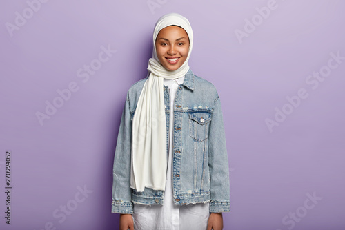 Valokuva  Half length shot of glad Arabian woman wears white hijab, denim jacket, expresses good emotions, has charming smile on face, stands against purple background