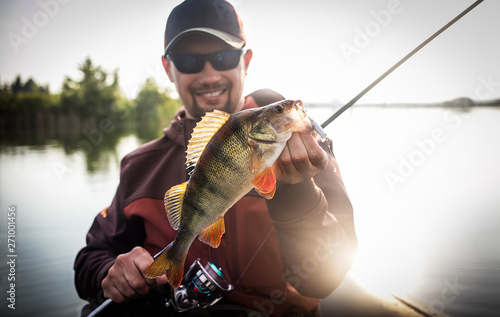 Fotografia, Obraz Happy angler with perch fishing trophy.