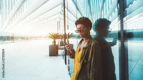 Foto  A charming African businesswoman in eyeglasses near the glass wall outdoors is u