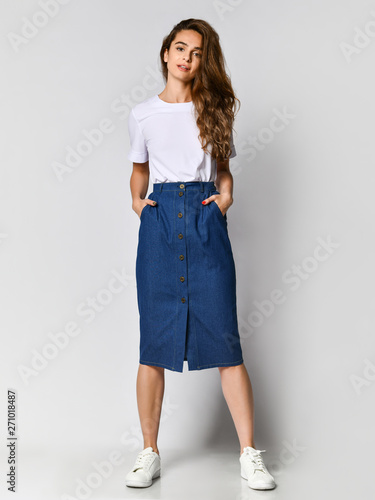 Fototapeta Full-length photo of a young brunette girl with long hair in a white blouse and blue skirt