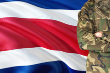 Crossed Arms Soldier With National Waving Flag On Background - Costa Rica Military Theme.