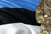 Crossed Arms Estonian Soldier With National Waving Flag On Background - Estonia Military Theme.
